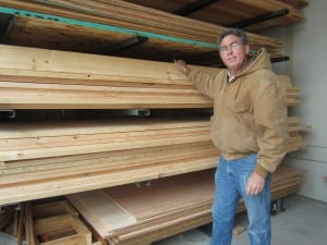 Randy Hughey inspects the spruce boards after they've been barged from Prince of Wales. (SCS photo)