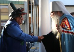 Native elders greets Metroplitan Tikhon on the steps of St. Michael's Cathedral. (KCAW photo/by Emily Forman)