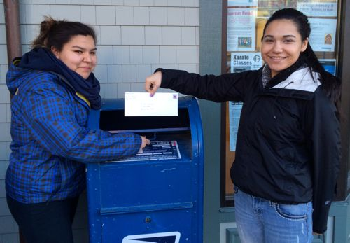 Pacific High School students Tatyanna Isaacs and Jenny Jeter mail proceeds from an Indian taco fundraiser to the Friends of Edna Adan University Hospital in Somaliland. (PHS photo)