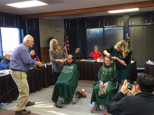 A well documented haircut: high school students Salma Zakiyah and Rosie Palof had their heads shaved as part of a fundraiser for the St. Baldrick's Foundation, at Tuesday night's meeting of the Sitka Assembly. (KCAW photo/Rachel Waldholz)