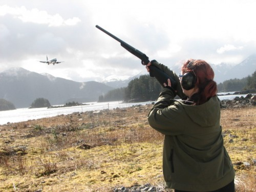 Wildlife specialist Heather Bauscher, uses a shotgun loaded with pyrotechnic shells to chase eagles off of Sitka's runway.(KCAW photo/by Emily Forman)