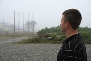 Lt. Lance Leone looks at five power poles that once anchored electrical wires across a channel near La Push. A Coast Guard helicopter bearing Leone and three others hit the wires and crashed in 2010. Leone was the only survivor. (Photo: Ed Ronco/KPLU)