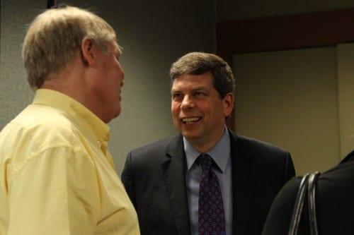 U.S. Senator Mark Begich speaks to Sitka resident Dirk White at the Sitka Chamber of Commerce. (KCAW photo/Rachel Waldholz)