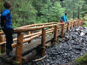 Hikers on the Herring Cove Trail footbridge. Flood waters pushed rocks under most of the span, turning it into a dam. (KCAW photo/Robert Woolsey)