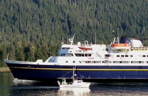 A Petersburg fishing boat passes the ferry Taku near the entrance of Wrangell Narrows in August, 2013. Budget cuts will take the ship out of service from July through September. (Photo by Ed Schoenfeld/CoastAlaska News)