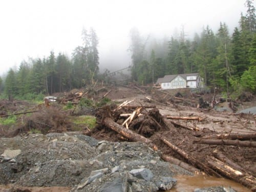 A new home under construction on Sitka's Kramer Avenue was totally obliterated in the slide. A neighboring new home stands unscathed. Four people remain missing . (NOAA/NWS photo, Joel Curtis)