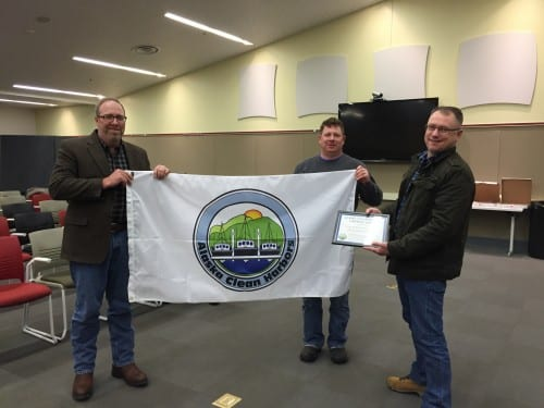 "From L to R: Chuck Hackett, Brett Farrell, and Stan Eliason hold the flag, designating Sitka as an ""Alaskan Clean Harbor."" (Emily Kwong/KCAW photo)"