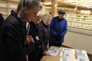 Commissioners Madeline Guhl, Jan Love, Alice Johnstone, and Jane Eidler look over photos of Sitka's last 13 libraries. (KCAW photo/Robert Woolsey)