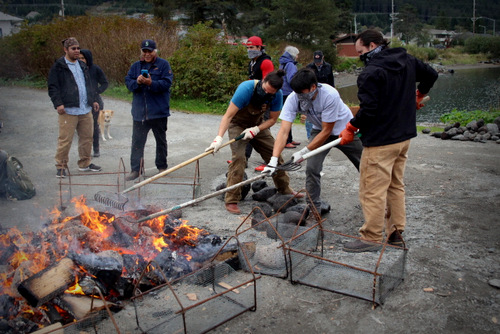 Carvers rake back the embers to reveal the heated lava rocks, which they'll shovel into the metal baskets. (KCAW Photo/Emily Russell)