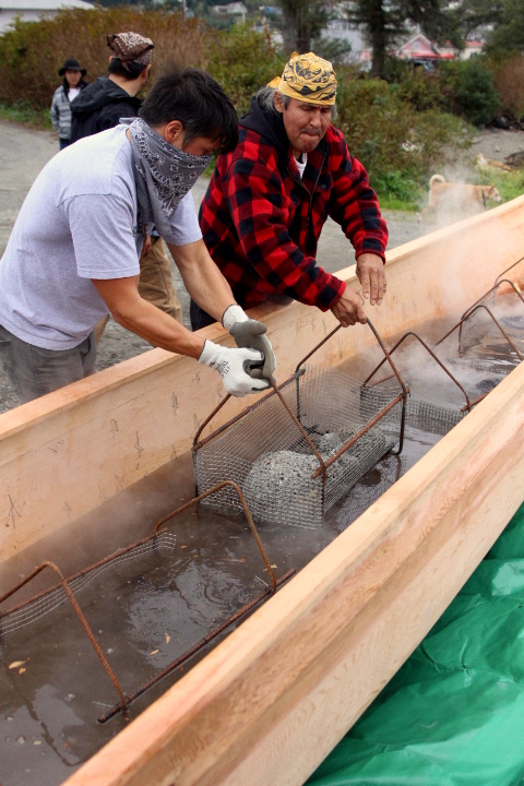 Jerrod Galanin gets help lowering a basket of hot lava rocks into the canoe. (KCAW Photo/Emily Russell)