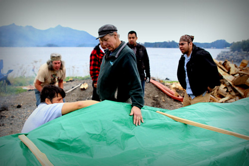 Master carver Steve Brown oversaw the steaming, while Jerrod Galanin takes a look under the tarp. (KCAW Photo/Emily Russell)