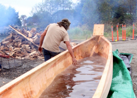 Tommy Joseph feels the warm water after the batch of lava rocks are taken out. (KCAW Photo/Emily Russell)