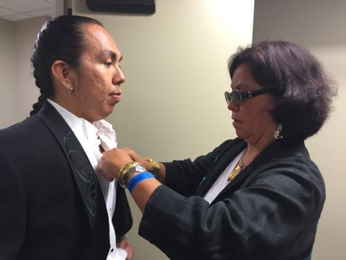 Dorothy Grant straightens the jeweled buttons on the Eagle/Raven tuxedo, modeled by Conrad Frank. Grant designed the piece for First Nations actor Duane Howard to wear to the 2015 Oscars. (Emily Kwong/KCAW photo)