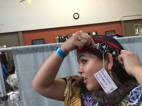 """Dickson beads some of her head bands with gold or porcupine quills. After studying fashion in Vancouver, she became interested in the traditional side of sewing and learned from elders. """"I picked up a beading needle and haven't been able to put it down since,"""" Dickson said. (Emily Kwong/KCAW photo)"""