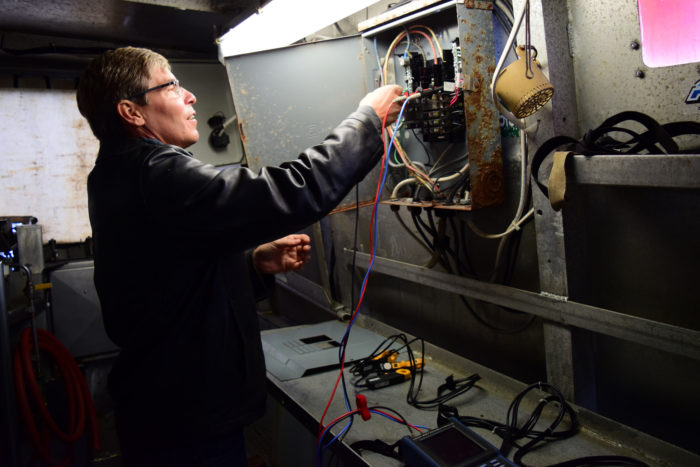 Mike Gaffney connects the power quality analyzer to the fishing vessel's electric panel. (Photo courtesy of Sustainable Southeast Partnership/Bethany Goodrich.)