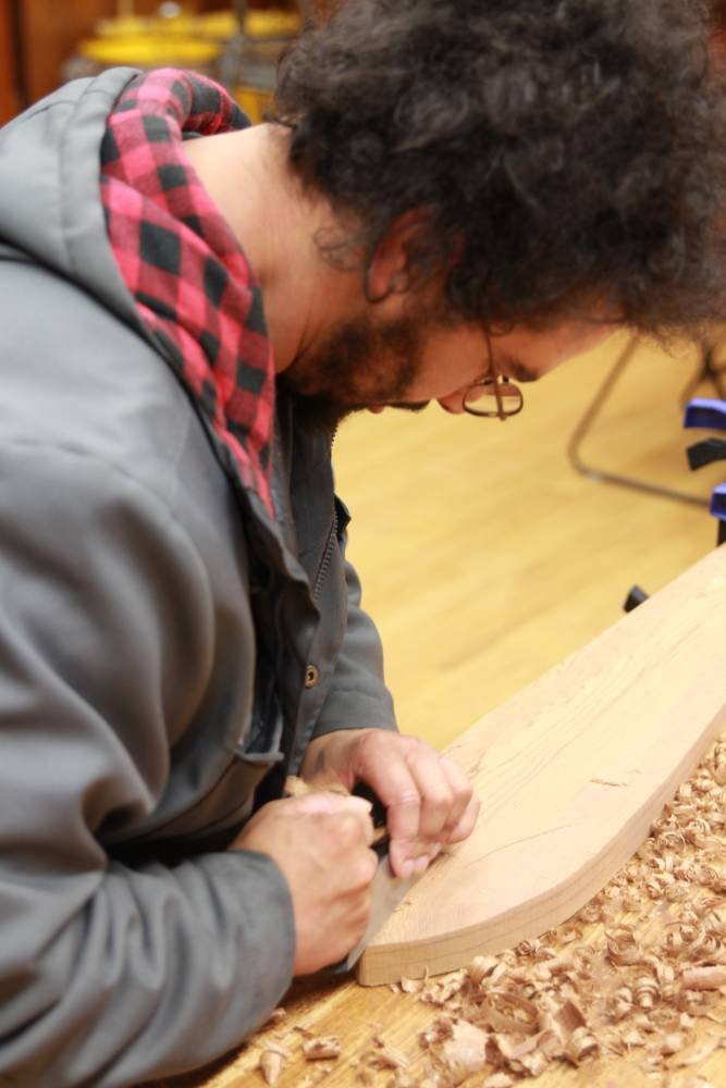 Pacific High School senior Daniel Abril focuses his efforts on the tip of a paddle he's been carving at the Sitka National Historical Park's visitor center for weeks.