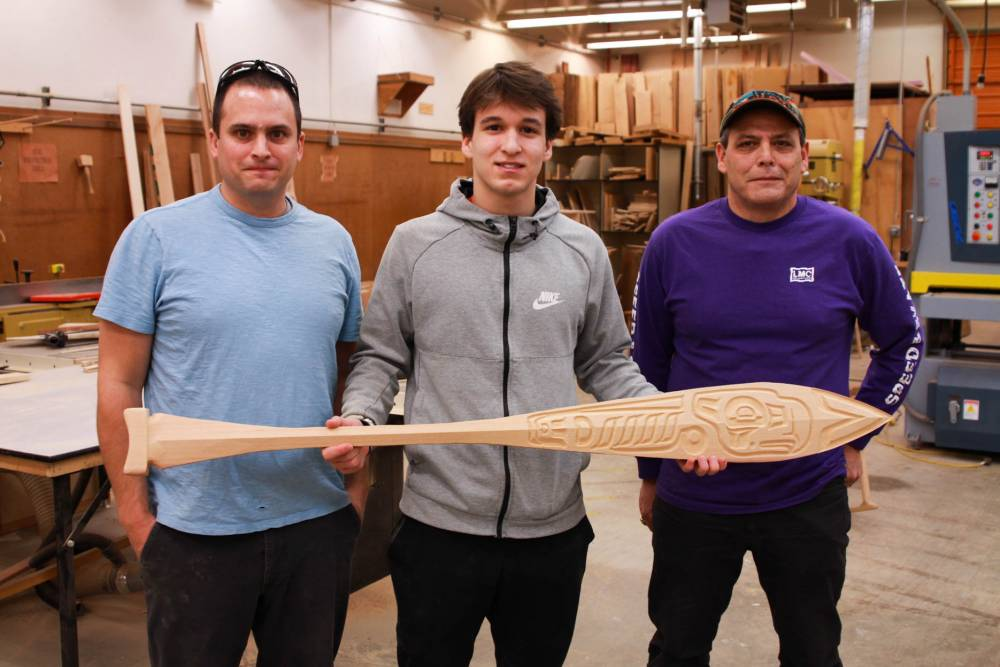 Sitka High School junior Asa Demmert, center, shows off his nearly-finished paddle featuring an eagle alongside Sitka High design instructor Mike Vieira, left, and STA traditional arts instructor, Charlie Skultka, right. (KCAW Photo / Enrique Pérez de la Rosa)